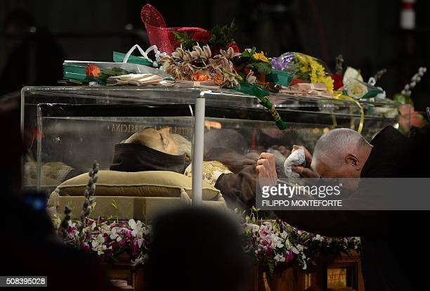 A monk prays in front of the exhumed body of mystic saint Padre Pio in the Catholic church of San Lorenzo fuori le Mura in Rome on February 4 2016...