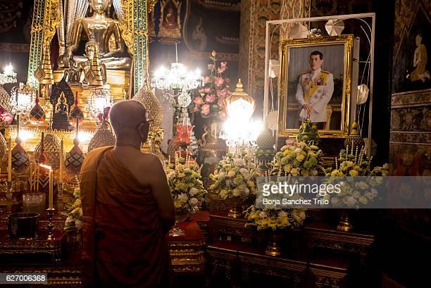 A monk prays in front of the portrait of His Majesty King Maha Vajiralongkorn Bodindradebayavarangkun at Wat Pathum Wanaram after his proclamation as...
