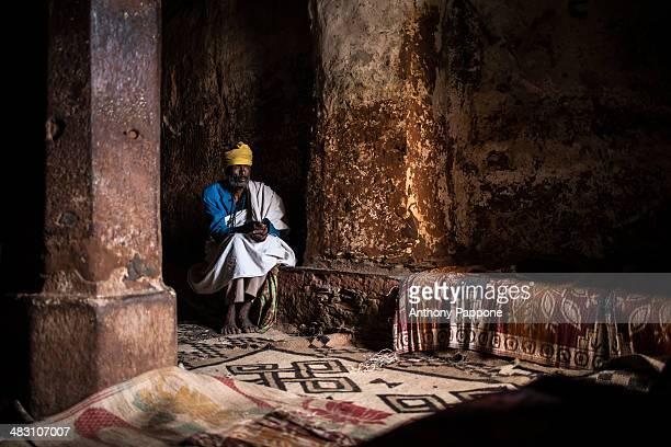 Monk prays inside a rock church in gheralta area, tigray, ethiopia