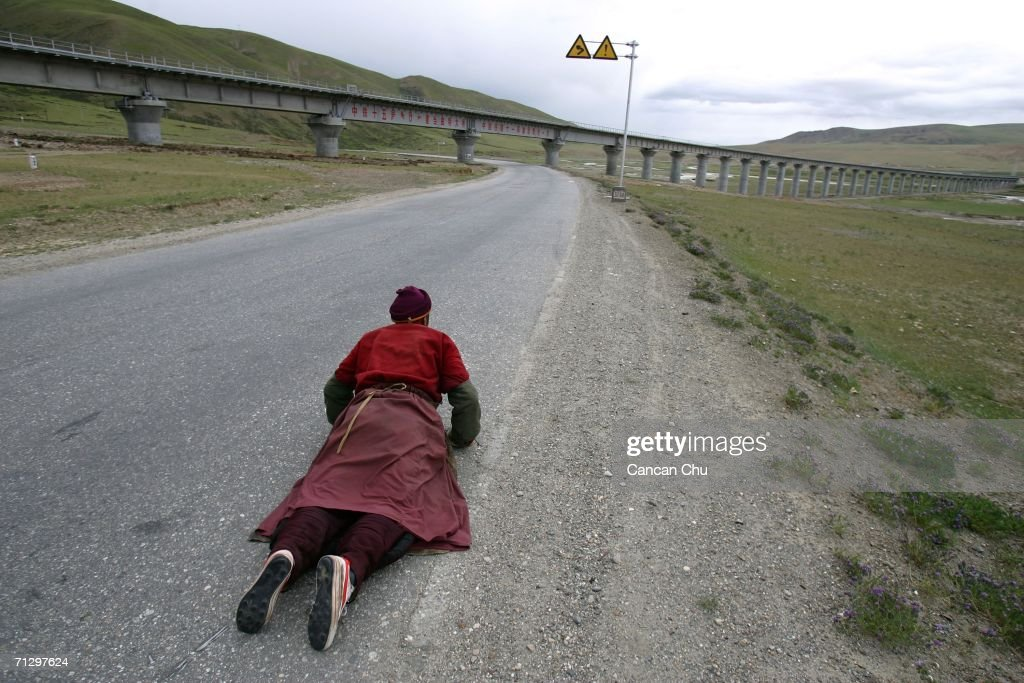 A monk prays near a railroad bridge of the Qinghai-Tibet Railway as they make their pilgrimage to Lhasa, the sacred Buddhist center for pilgrims, on June 25, 2006 in Dangxiong County of Lhasa, Tibetan Autonomous Region, China. The Qinghai-Tibet railway will begin trial operations on July 1 and schedule has been set for the first five trains to Tibet via the new railway, an official with the Qinghai-Tibet Railway Company said. The 1,956-kilometer-long (about 1,215 miles) Qinghai-Tibet railway, linking Xining, capital of Qinghai Province, with Lhasa, capital of Tibet Autonomous Region, is the world's highest and longest plateau railroad and also the first railway connecting Tibet with other parts of China. Some 960 kilometers (576 miles) of its track are located 4,000 meters (13,120 feet) above sea level and the highest point is 5,072 meters (16,636 feet), according to state media.
