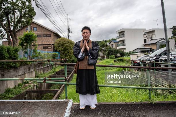 A monk prays near the Kyoto Animation Co studio building after an arson attack on July 19 2019 in Kyoto Japan Thirty three people are believed dead...