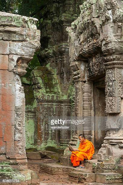 monk reading at ruins - angkor stock photos and pictures