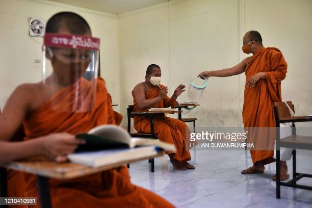 A monk receives a face shield as a preventive measure against the spread of the COVID19 coronavirus from the abbot during religious studies at Wat...