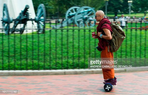 A monk rides a hoverboard as he passes near the White House in Washington DC August 16 2018