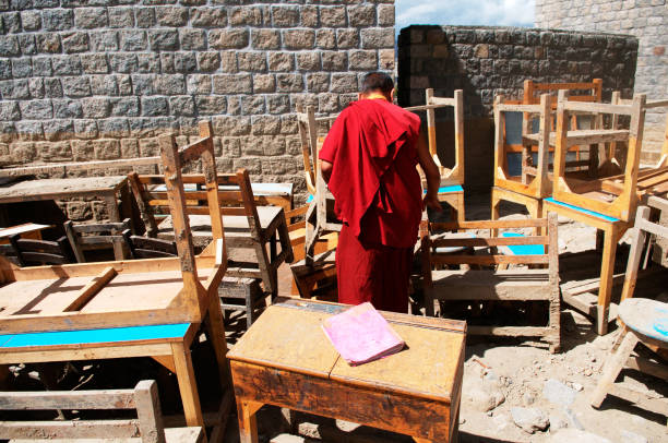 Monk searching books in damaged dpk institute due to flashflood in leh, Ladakh, Jammu and Kashmir, India
