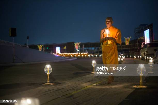 Monk seen walking around the temple while holding a lantern during the yearly Makha Bucha ceremony in the north of Bangkok. Buddhist devotees...