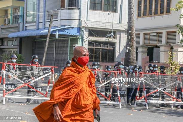 Monk seen walking in front of a barricade with police officers during the military coup protest in Mandalay. A massive crowd took to the streets of...