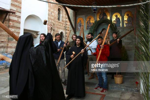 Monk shows to Orthodox Christian worshippers use an old traditional wood and wooden hammer toll which has been used for centuries to announce time...