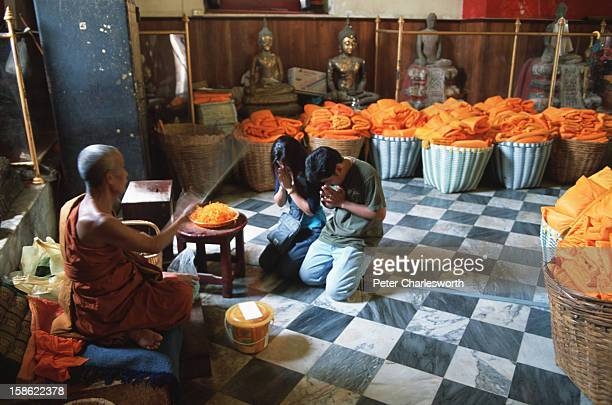 A monk sits and splashes holy water on worshippers who kneel amidst baskets of saffron robes that can be purchased for merit making at the Thai...
