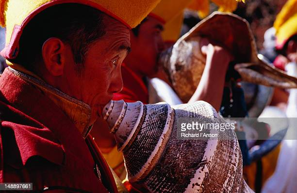monk sounding conch shell at mani rimdu festival. - mani rimdu festival stock pictures, royalty-free photos & images