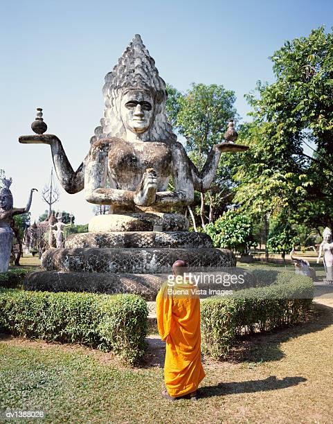 Monk Standing by a Statue of the Buddha, Vientiane, Mekong Valley, Laos