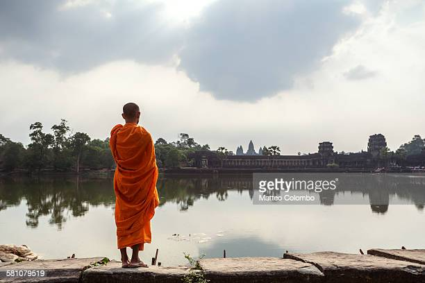 monk standing in front of angkor temples, cambodia - monk stock pictures, royalty-free photos & images