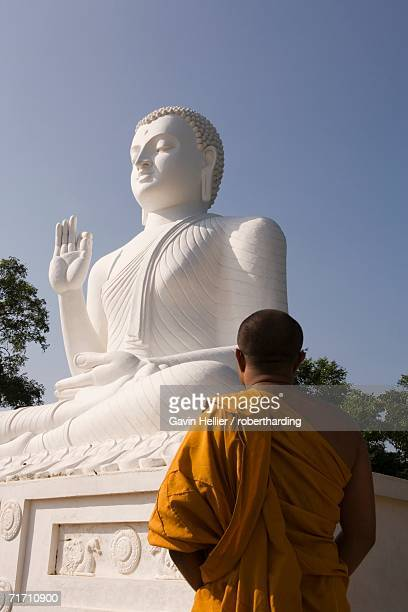monk standing in front of the great seated figure of the buddha, mihintale, sri lanka, asia - mihintale stock pictures, royalty-free photos & images