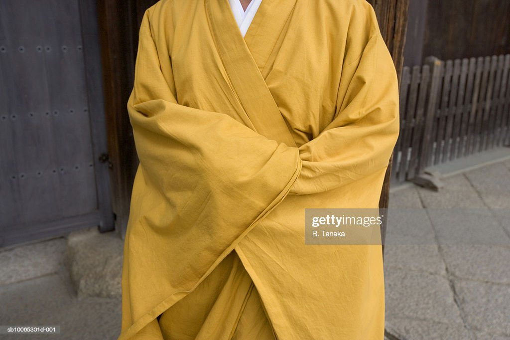 Monk standing in yellow robe, mid section : Foto stock