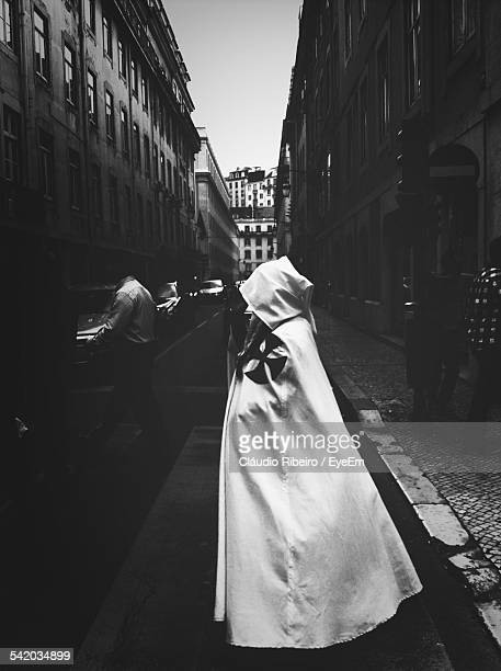 monk standing on city street - maltese cross stock photos and pictures