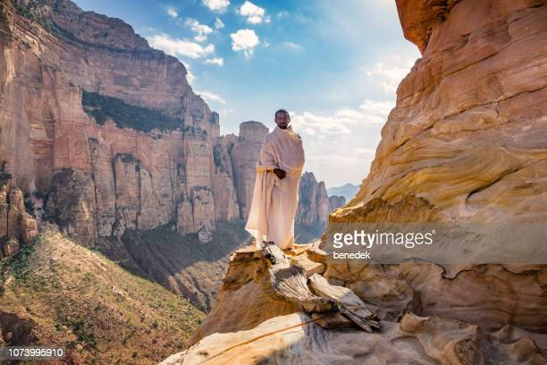 monk stands at abuna yemata guh monolithic church in hawzen tigray region ethiopia - ethiopia stock pictures, royalty-free photos & images