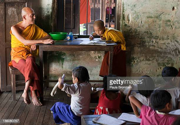 A monk stands in for a teacher as children and monks study together at a school run by a monastery December 15 2011 in Bago Myanmar The education...