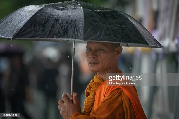 A monk takes cover from torrential rain as people begin to queue and sleep on the streets overnight to attend Thailand's late King Bhumibol...