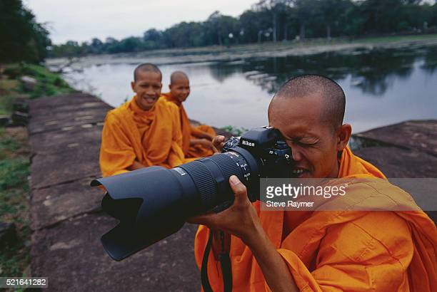 monk taking pictures near angkor wat - nikon stock pictures, royalty-free photos & images