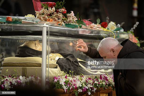 A monk touches the glass where the exhumed body of the mystic saint Padre Pio lies in the Catholic church of San Lorenzo fuori le Mura in Rome on...