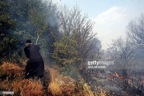 A monk tries to extinguish a fire using a branch in the village of Ano Kotili on Peloponnese peninsula 30 August 2007 Greece battled devastating...