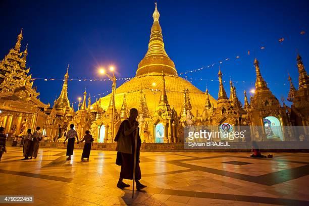 CONTENT] Monk walking around the Shwedagon paya by night Rangoon or Yangon in Burma also called Myanmar