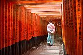 Monk walking in Fushimi inari shrine path of torii