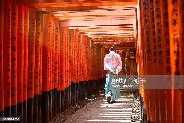 Monk walking in Fushimi inari shrine path of torii