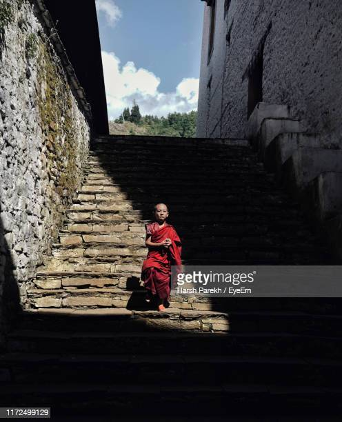 monk walking on staircase - bhutan stock pictures, royalty-free photos & images