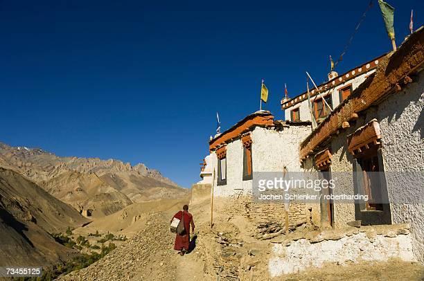 Monk walking past Lamayuru gompa (monastery), Lamayuru, Ladakh, Indian Himalayas, India, Asia