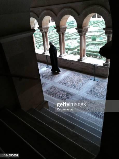 Monk walking through the cloister of the romanesque monastery of Santo Domingo de Silos, Burgos, Castile and Leon, Spain.