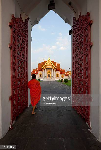 monk walking through the entrance, marble temple,bangkok. - wat benchamabophit stock photos and pictures
