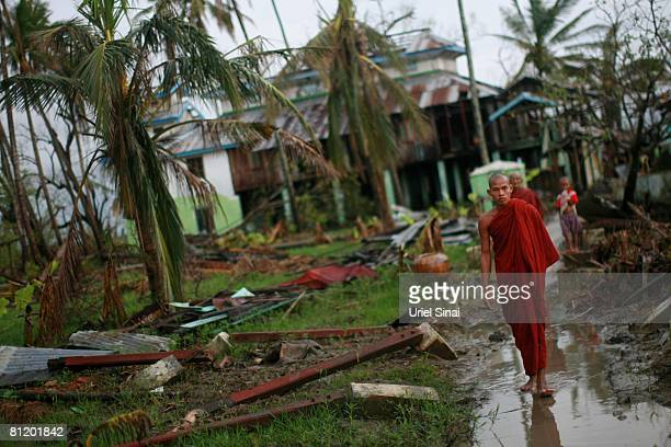 A monk walks by his damaged monastery May 20 at the isolated village of Mingala Taungtan in the Ayeyarwaddy delta Myanmar It has been estimated that...
