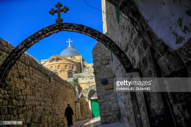 TOPSHOT A monk walks near the Church of the Holy Sepulchre before the start of the Easter Sunday service amid the coronavirus disease outbreak in...