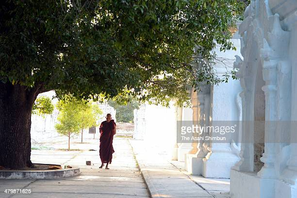 A monk walks outside the Kuthodaw Paya on January 17 2014 in Mandalay Myanmar Richly colored murals and pagodas which built in 11th to 13th century...