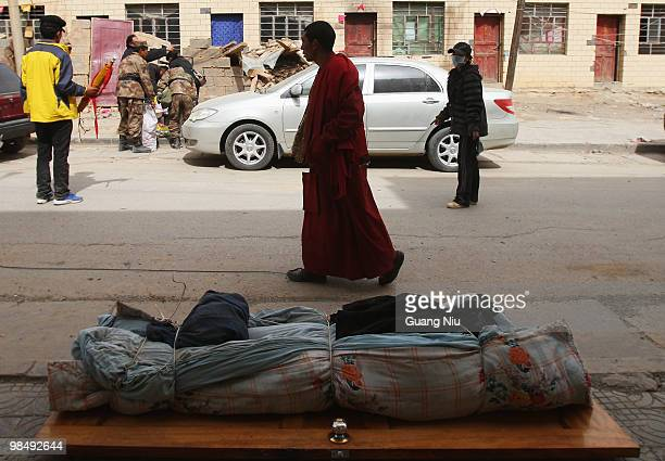 Monk walks past a body wrapped and waiting for collection following a strong earthquake, on April 16, 2010 in Jiegu, near Golmud, China. It is...