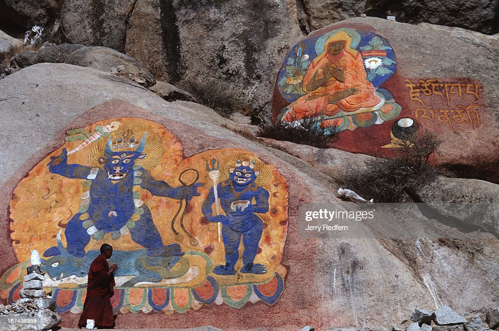 A monk walks past large painted rock carvings on the mountains overlooking town..