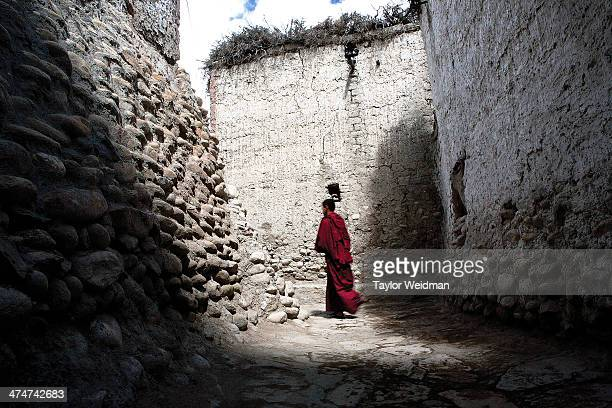 A monk walks through the alleyways of Lo Manthang Hidden in the rain shadow of the Himalaya in one of the most remote corners of Nepal lies Mustang...