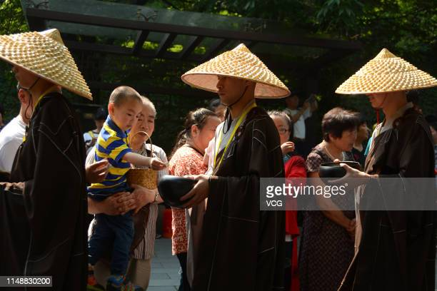 Monk wearing a straw hat and holding an alms bowl receives alms from a child on the way to Lingyin Temple during the Buddha's birthday on May 12,...