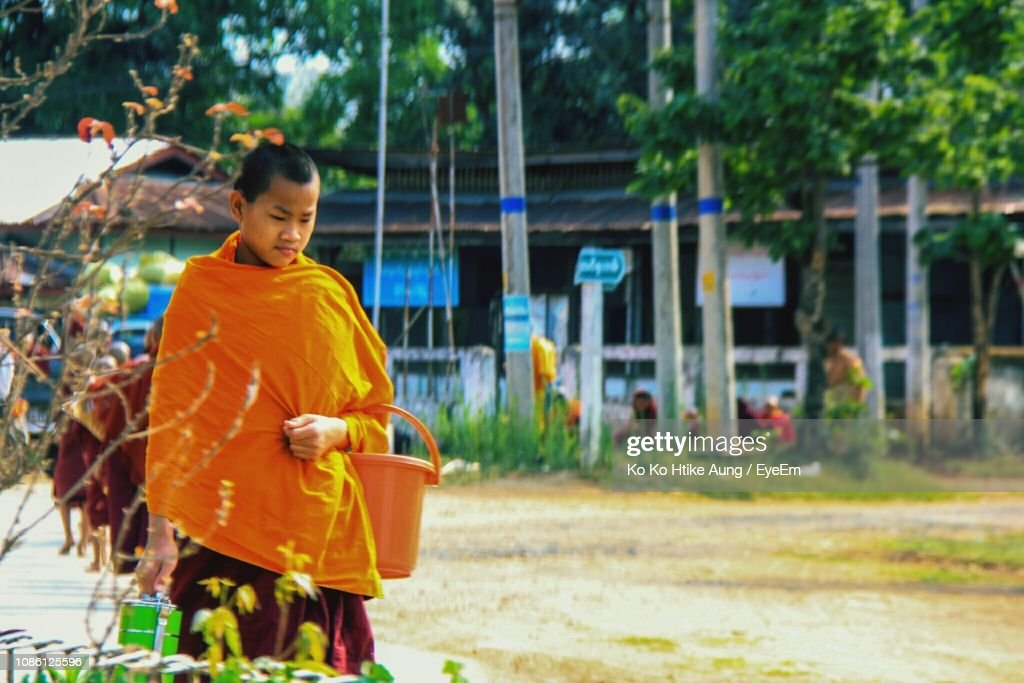 Monk Wearing Traditional Clothing Standing On Field : Stock Photo