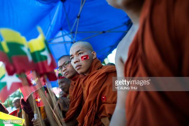 TOPSHOT A monk wears a sticker of the Myanmar military flag on his face during a rally to show support to the Myanmar military in Yangon on October...