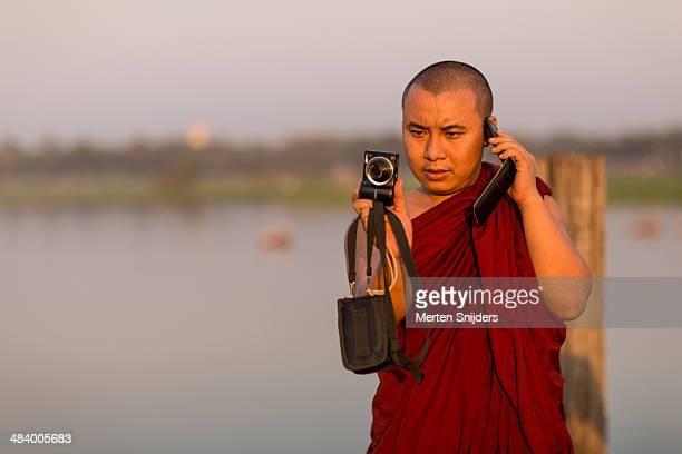 monk with phone and camera - merten snijders stock-fotos und bilder