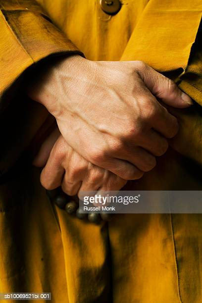 monk with prayer beads wrapped around one hand, mid section - monk stock pictures, royalty-free photos & images