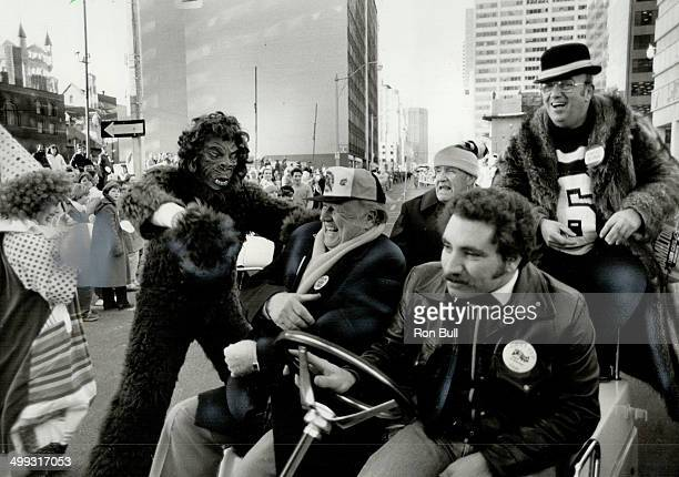 Monkey business Hamilton TigerCat owner Harold Ballard grins during yesterday's Grey Cup parade as a gorillacostumed figure lunges at him Behind...