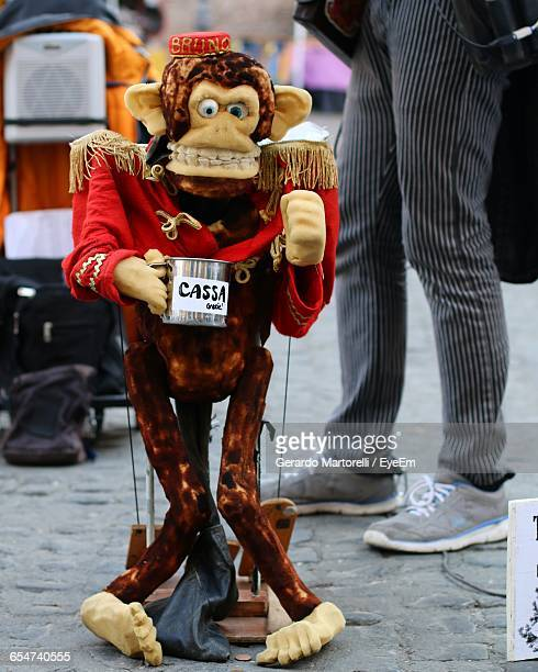 monkey toy begging on footpath - monkey shoes stock photos and pictures