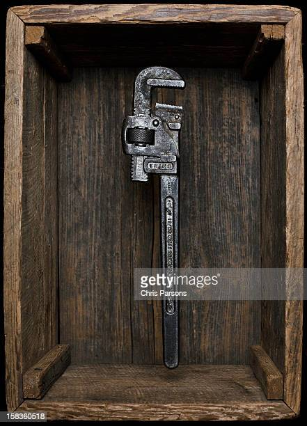 Monkey wrench floating in antique wooden box.