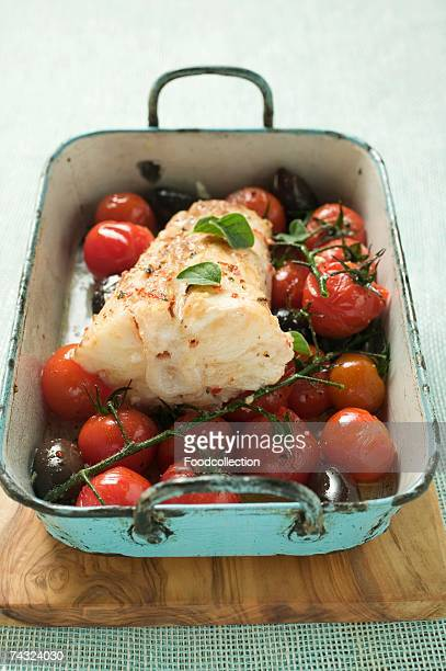 monkfish with cherry tomatoes and olives in roasting tin - アンコウ ストックフォトと画像
