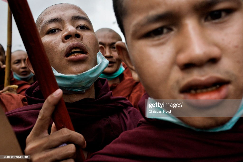 Monks and other protesters march on Pansodan Road as they head towards the Sule Pagoda on September 26, 2007 in Yangon, Myanmar. Later, there was a standoff a few hundred meters from the Pagoda after heavily armed military soldiers, blockading the road, fired warning shots. The group stopped at the intersection to chant and pray for over an hour before continuing their march away from the Pagoda. People fled to flats and shops when warning shots were fired. Allegedly one person was killed and five injured at the beginning of today's march at nearby Shwedagon Pagoda. Mass protests began after the military government implemented dramatic price hikes in fuel prices on August 15th causing public bus fares to double and widespread economic hardship. The monks became involved when the leadership of initial protest marches were supressed. Uniformed security personnel were positioned throughout the former capital, patrolling watching crowds, telling them to not get involved lest action be taken against them. Military trucks parked less than a kilometer from City Hall and the Sule Pagoda, the plaza between the two buildings where in 1988, the government crushed similar pro-democracy protests by killing up to 3000 pro-democracy protesters. Government opposition has been repeatedly crushed in the country and the latest demonstrations have yet again led to mass arrests of political activists opposing the regime.