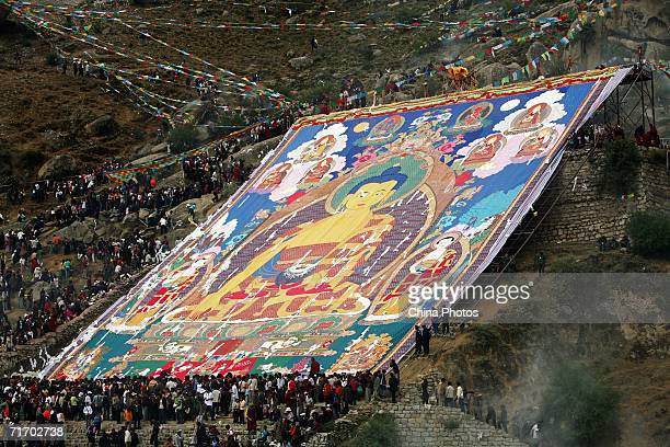 Monks and pilgrims unveil a huge image of Sakyamuni at the Sunning Buddha Ceremony to mark the Shoton Festival at Drepung Monastery on August 23 2006...