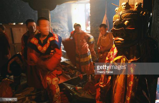 Monks are getting dressed with traditional cloth and mask in the dressing room of the Tawang monastery during the Torgya festival